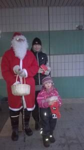 Kinkkuarvonnan voittajat Saima Kiero ja Oili Harjula joulupukin kanssa yhteispotretissa. Kuvasta puuttuu Jyri Säyriö, joka oli vielä metsässä etsimässä rasteja.