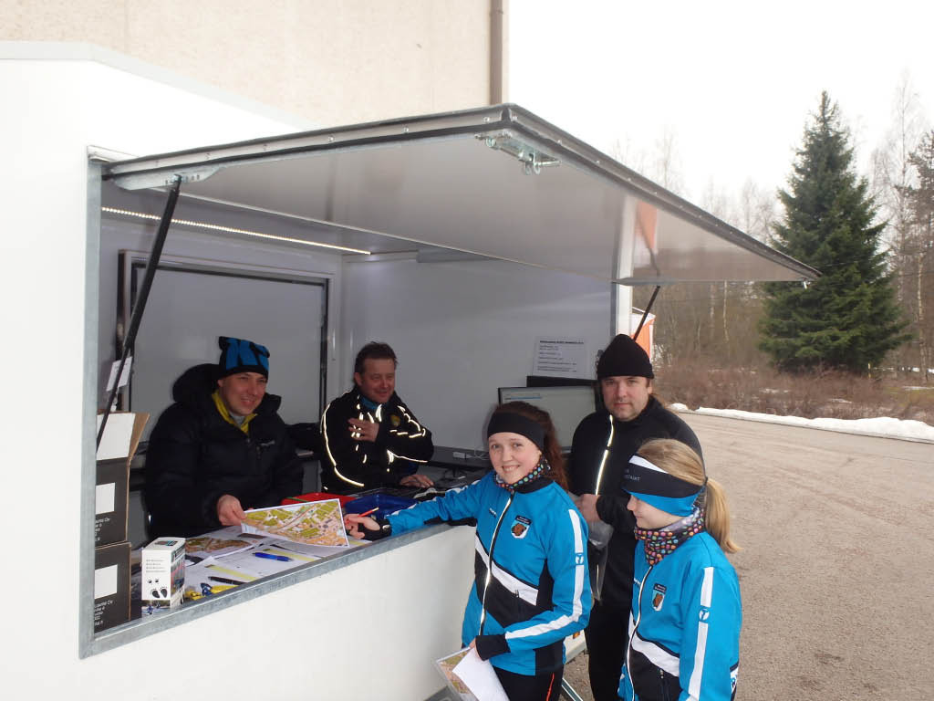 Tyytyväisiä asiakkaita kioskilla. Pinja Hietanen kirjautuu B-radalle, Liisa Peltonen jonottaa karttaansa ja Anssi Pajuoja jo kartta kädessä.