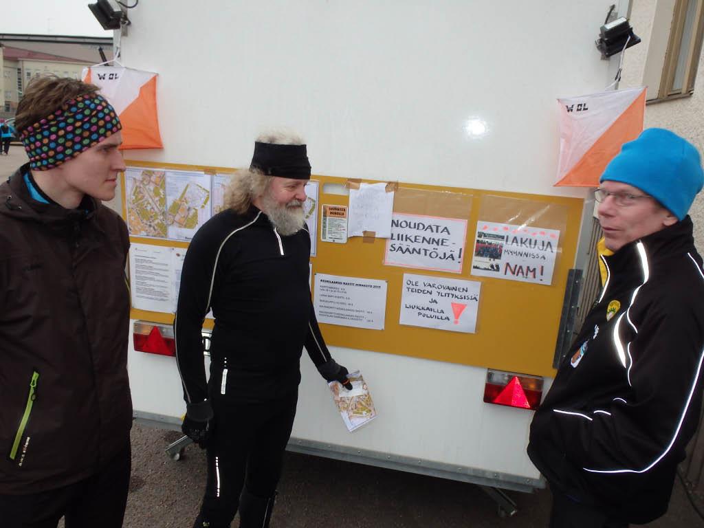Kioskin takaseinälle nostetaan ilmoitustaulu. Jukka Tani ja Jorma Sipilä katselevat viritystä. Jukka Sakki hieman apeana: ei hillomunkkeja, vain lakuja. NAM! mallikarttoineen
