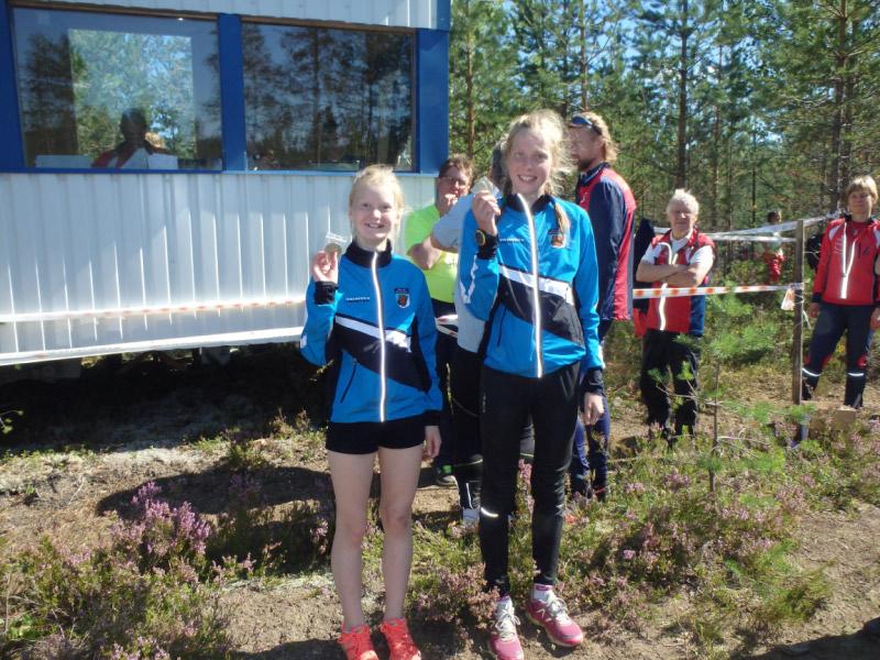 Nuorten Jukolassa suurimmat erot syntyvät tyttöjen osuuksilla. KS:llä on ykkösjoukkueessan nopeita tyttöjä. Tässä kuvassa Liisa Peltonen (3. osuus) ja Elisa Mattila (5. osuus) AM-kisojen kirkkaimpia mitaleita esittelemässä.