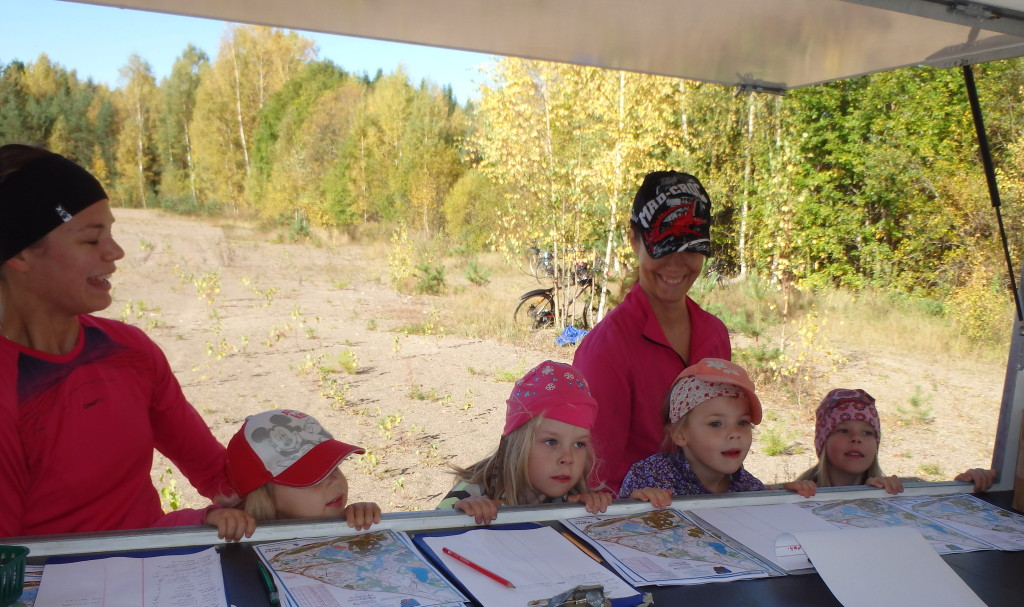 Säpinää karttatiskillä. Vasemmalta Kaisa  ja Silja Järnefelt, Lilka Tillman, Karoliina Tillman, Pihla Järnefelt ja Aava Tillman haluavat rastien hakuun.