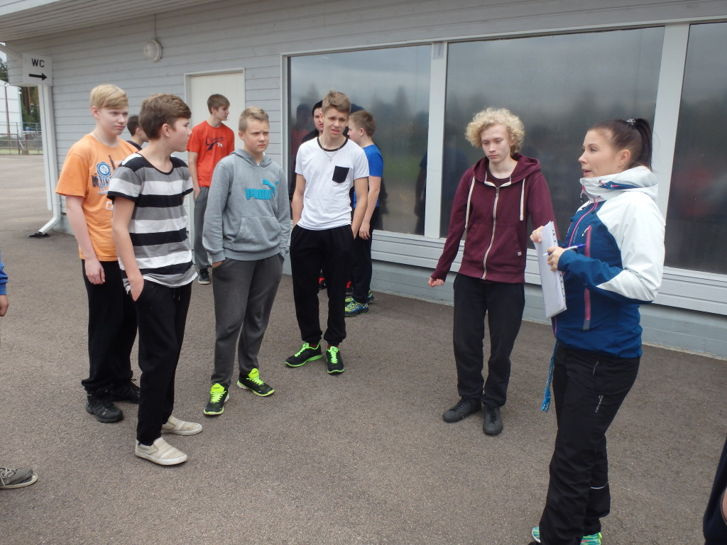 Liikunnanopettaja Minna Happonen kertoo yhdelle poikien ryhmistä liikuntatunnin teemasta.