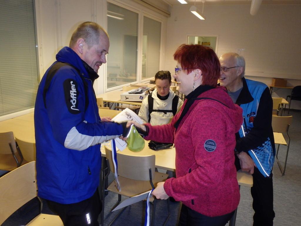 Sunnuntaiyönä klo 0.30 päivystysvuorossa ollut Virpi Hyyrynen luovuttaa kunniakirjan ja mitalin jälleen yhdelle raskaan hiihtourakan suorittaneelle osallistujalle.
