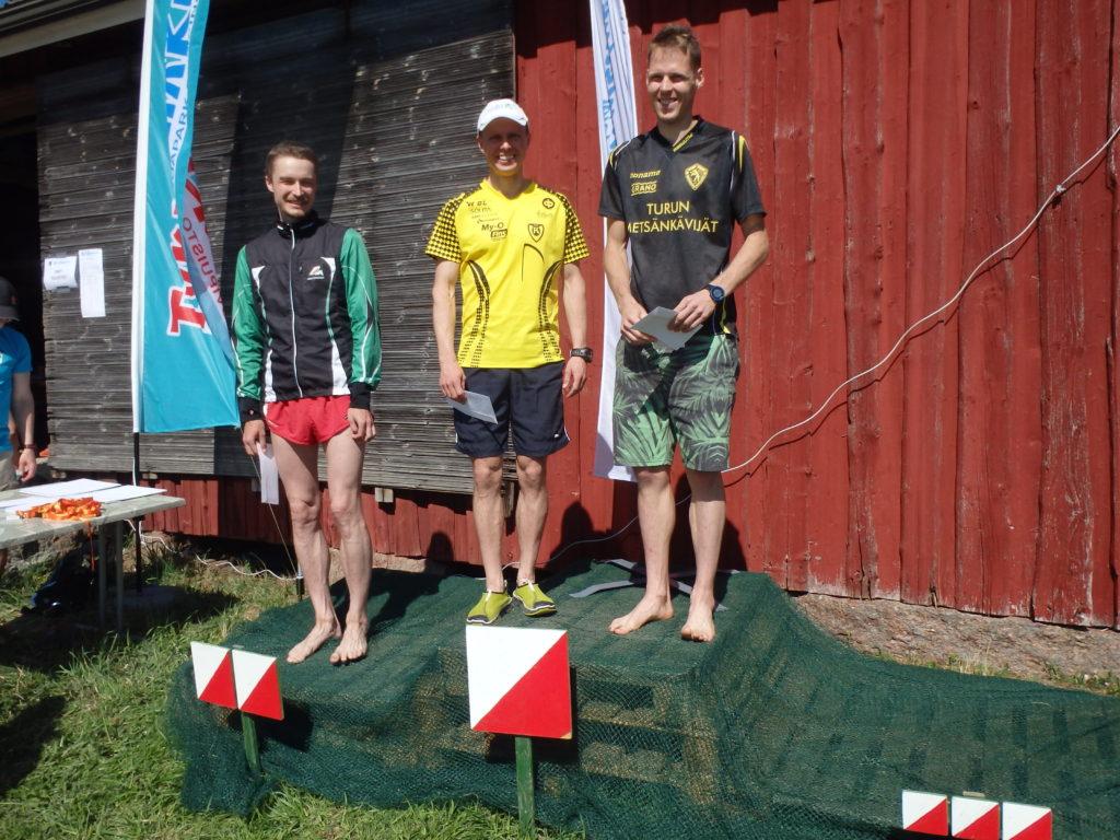 Ykköspallilla päivän voittaja Jani Lakanen sekä yhteistulosten paras Jussi Suna. Vieressä seuraa päivän kakkonen Denis Grisham.